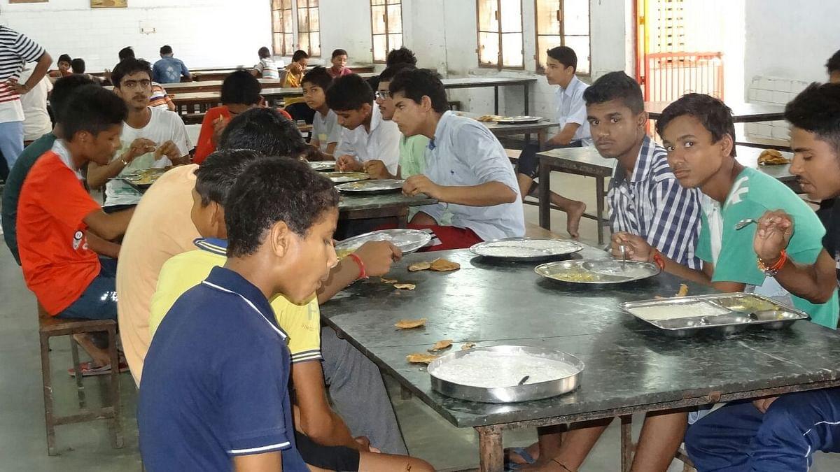 नवोदय विद्यालय में एक साथ बैठकर खाना खाते बच्चे