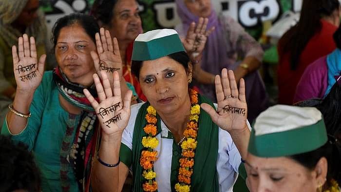 महिलाओं ने हाथ पर मेहंदी से किसान एकता लिखा