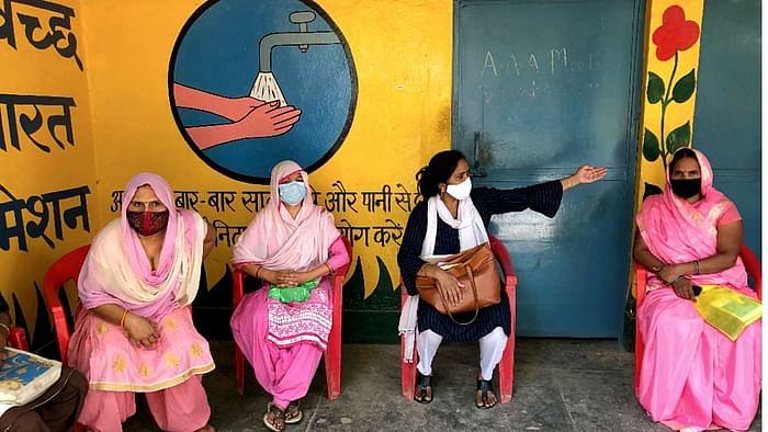 मेरठ के गागोल गांव में ग्राम प्रधान से मिलती आशा कार्यकर्ता