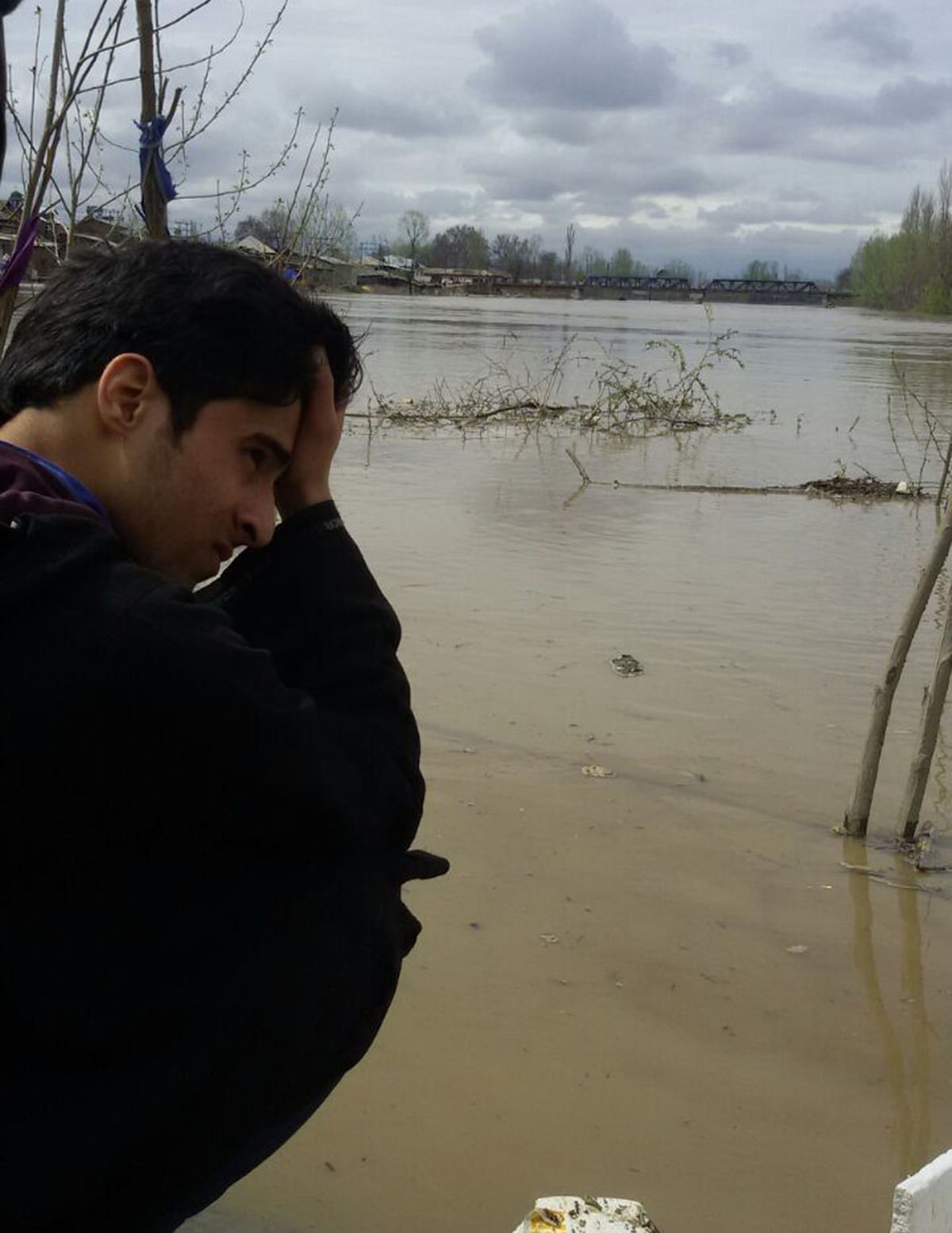 A Kashmiri youth examines the destruction sitting on the banks of river Jhelum in Pampore, 10 kms from Srinagar.  (Photo: Mohammed Mukarram)