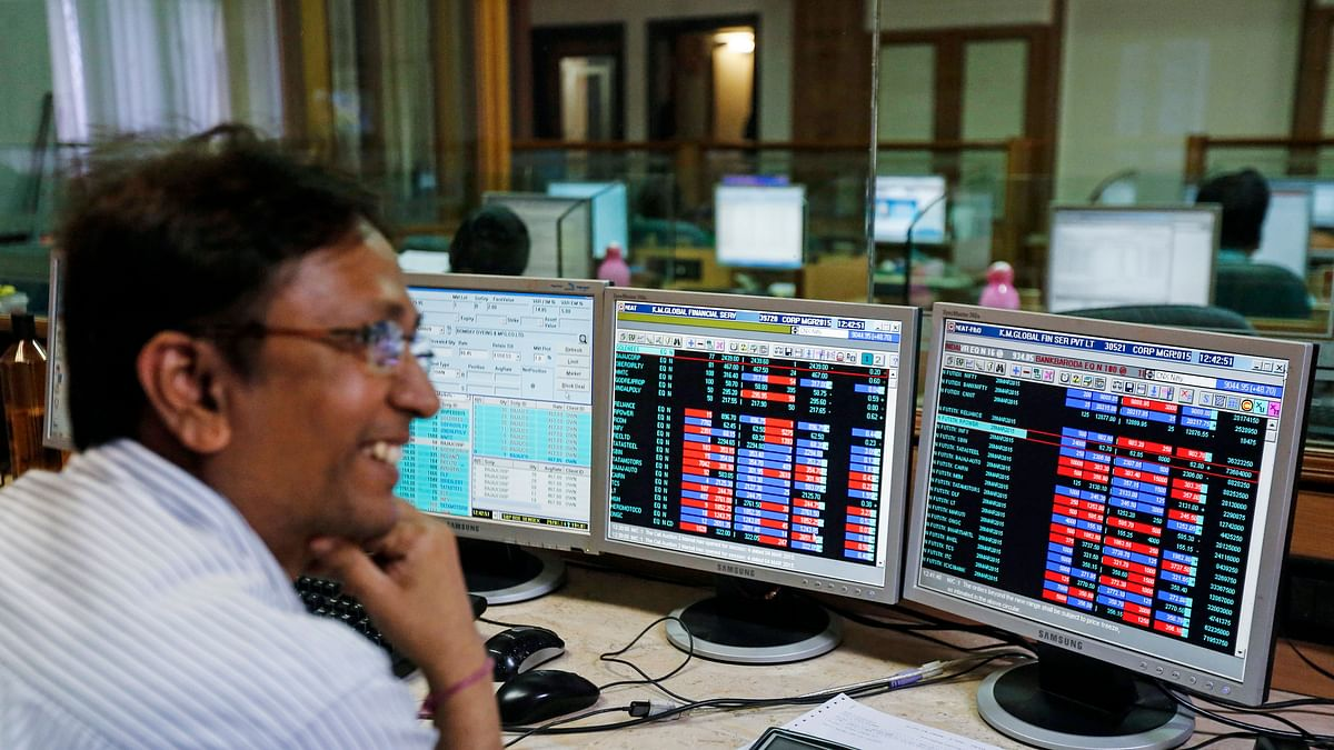 A broker laughs while speaking to a colleague, as they trade on their computer terminals at a stock brokerage firm in Mumbai, March 4, 2015. (Photo: Reuters)