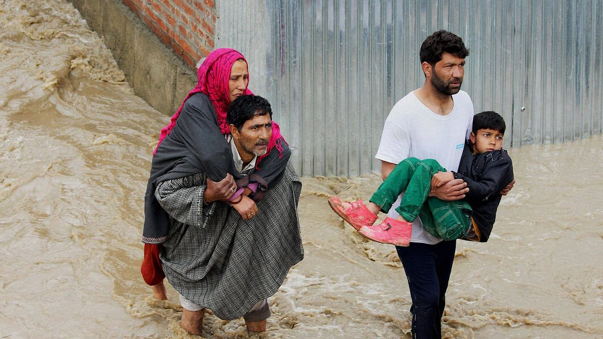 Jammu and Kashmir flood: A man carries his wife on his back as he wades through water (Photo: PTI)