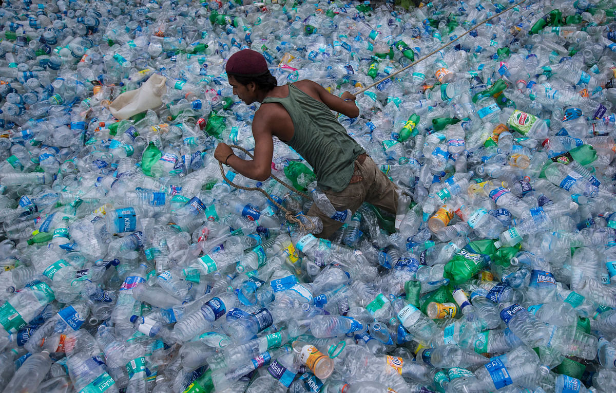 A worker  moves through a pile of empty plastic bottles at a recycling workshop in Goa. (Photo: Reuters)