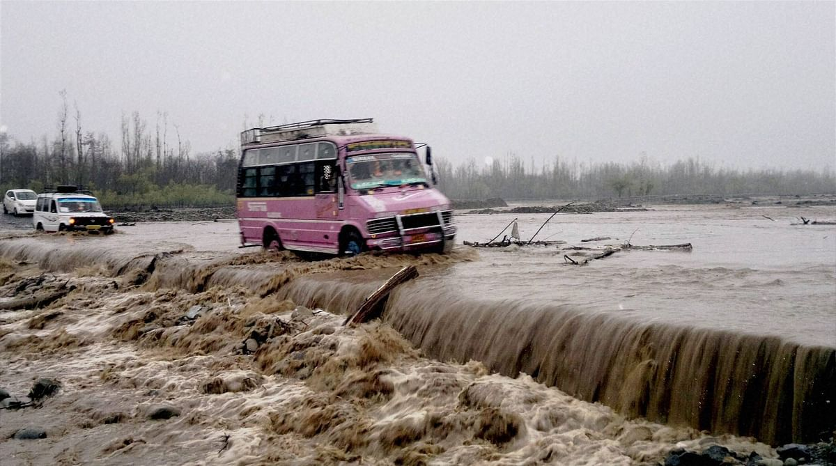 Vehicles pass through submerged bridge in a flooded Larkipora area in Anantnag, South Kashmir on Sunday. At least 10 people have died in the valley. Authorities have declared floods, second in less than 8 months. (Photo: PTI)