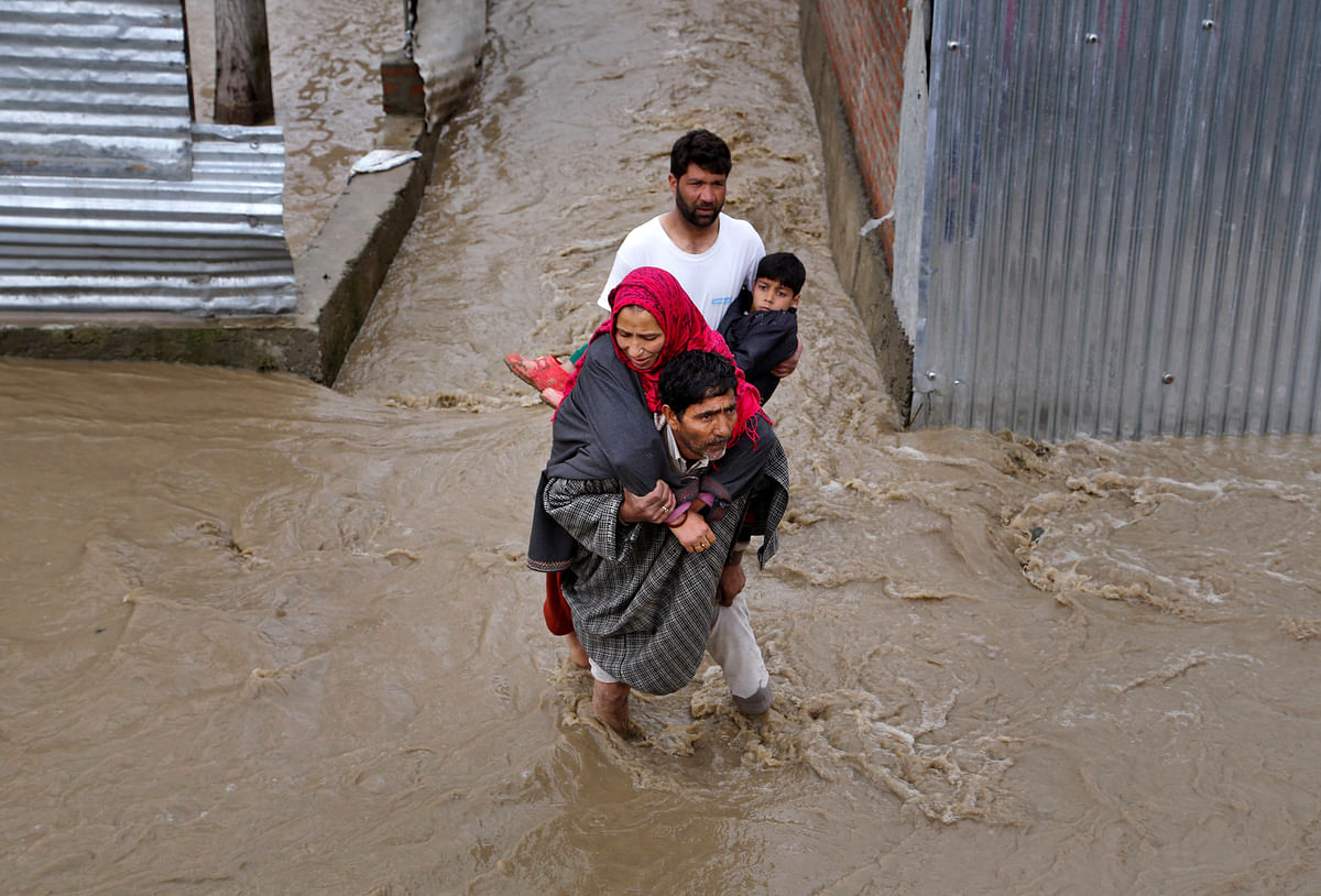 Men assist a woman and a child evacuate from a flooded area in Srinagar. (Photo: AP)