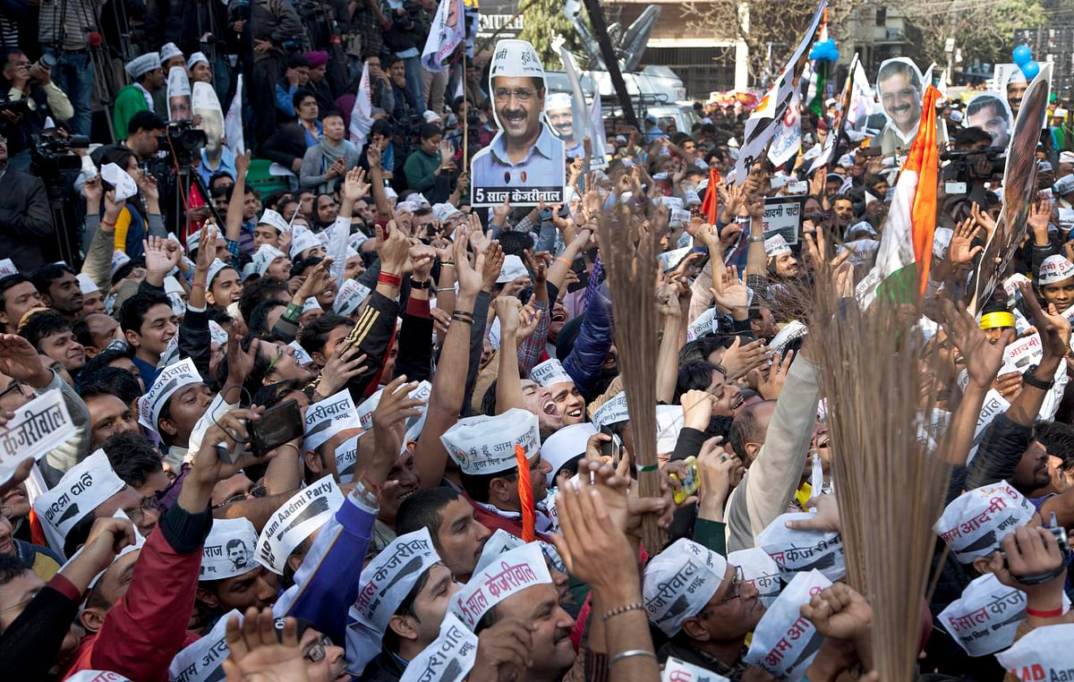 Supporters of the Aam Aadmi Party (AAP) hold cut-outs of their leader Arvind Kejriwal and their party symbol, the broom, as they celebrate the party's victory in New Delhi. (Photo: AP)