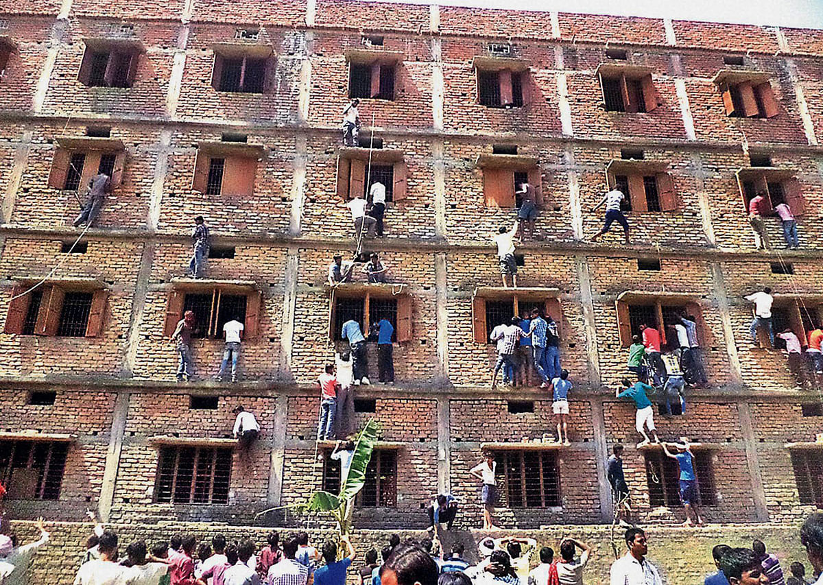 In this Wednesday, March 18, 2015 photo, Indians climb the wall of a building to help students appearing in an examination in Hajipur,Bihar. (Photo: AP)