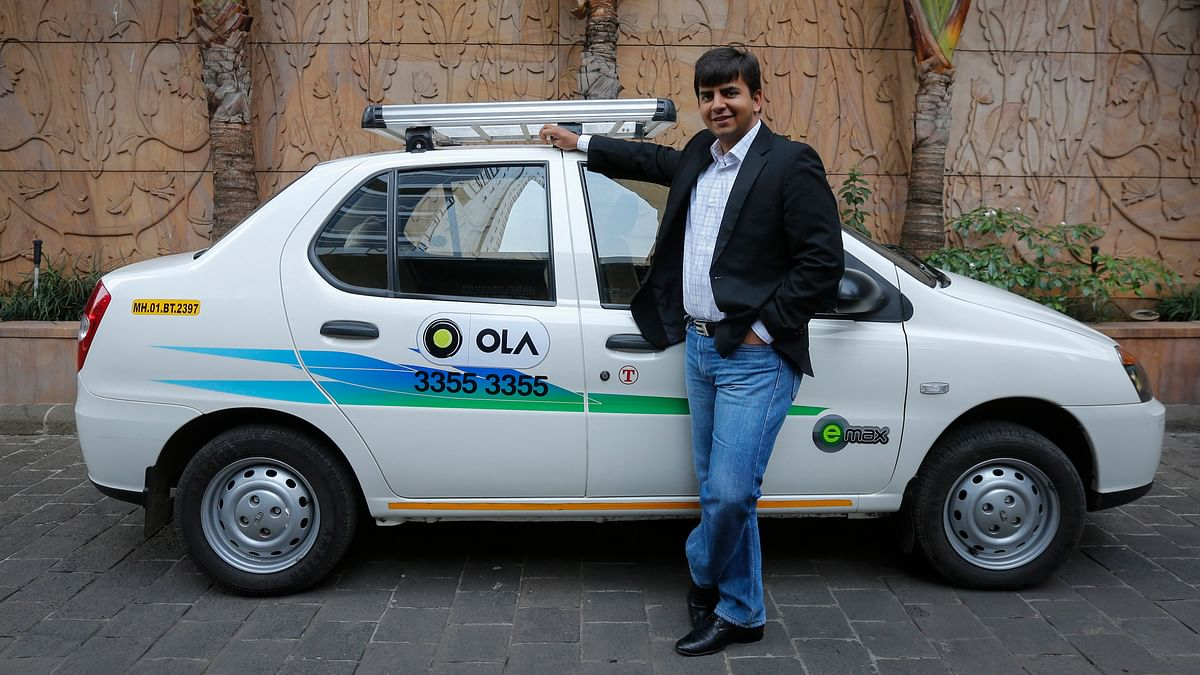 Bhavish Aggarwal, CEO and co-founder of Ola, an app-based cab service provider, poses in front of an Ola cab in Mumbai 3 March 2015. (Photo: Reuters)