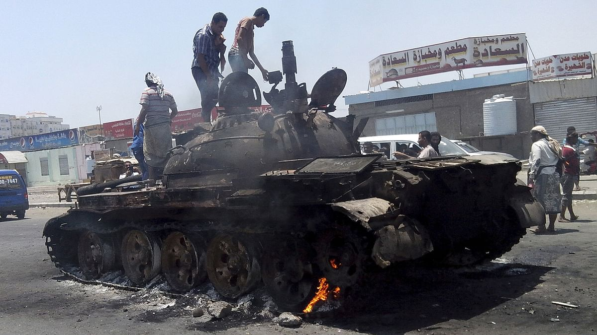 People stand on a tank that was burnt during clashes on a street in Yemen's southern port city of Aden. (Photo: )