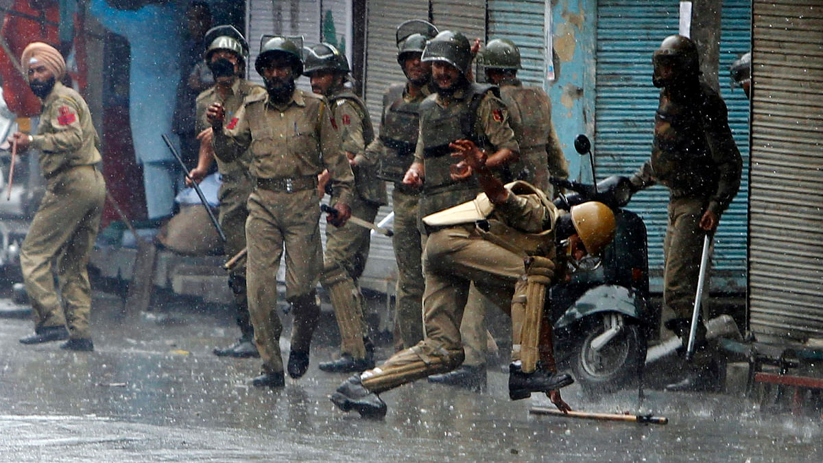 A policeman falls after throwing a piece of stone towards protesters in Srinagar. (Photo: Reuters)