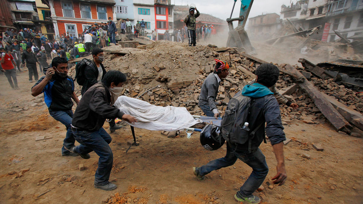 Volunteers carry the body of a victim on a stretcher, recovered from the debris of a building that collapsed after an earthquake in Kathmandu, Nepal.