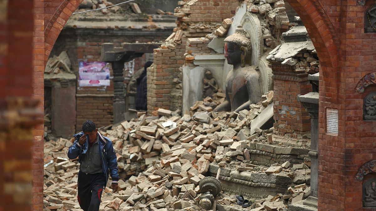 A man cries as he passes by a damaged statue of Lord Buddha in Bhaktapur, a day after the 2015 Nepal earthquake.