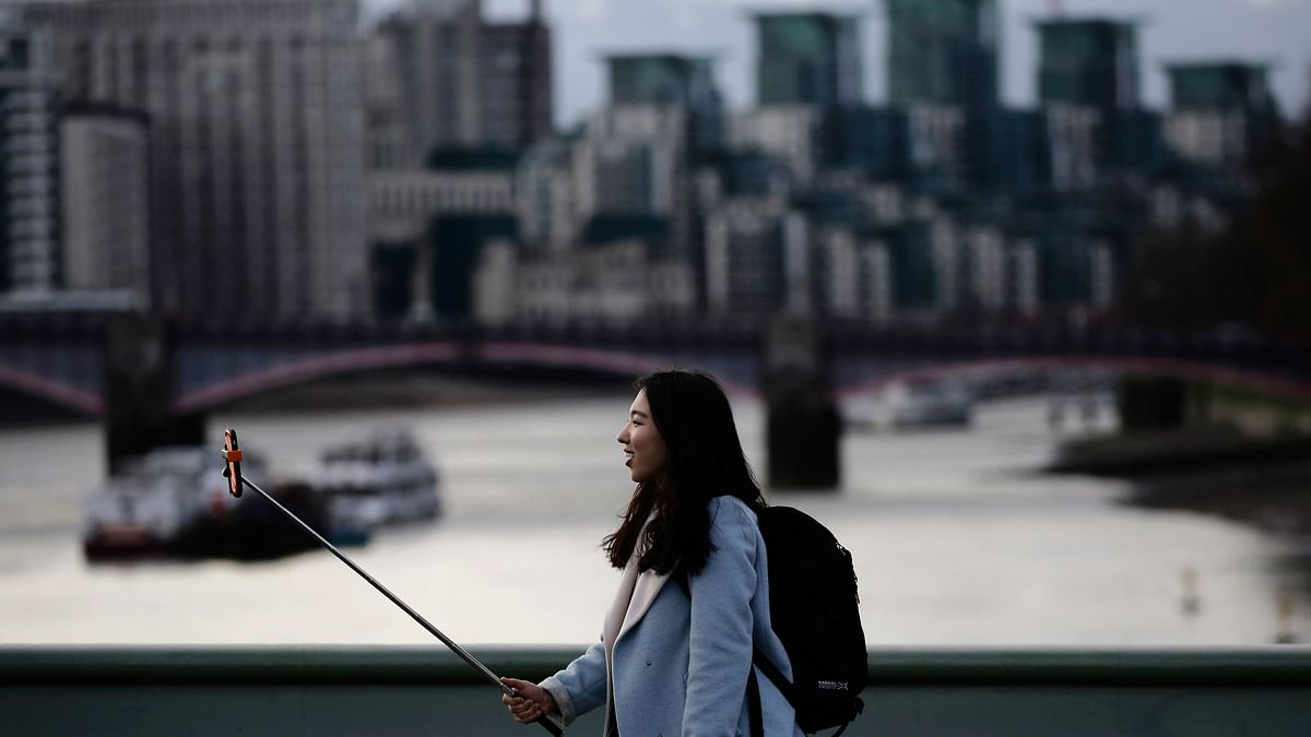 """A woman takes a photo using a """"selfie"""" stick whilst standing on Westminster Bridge in London, January 10, 2015. (Photo: Reuters)"""