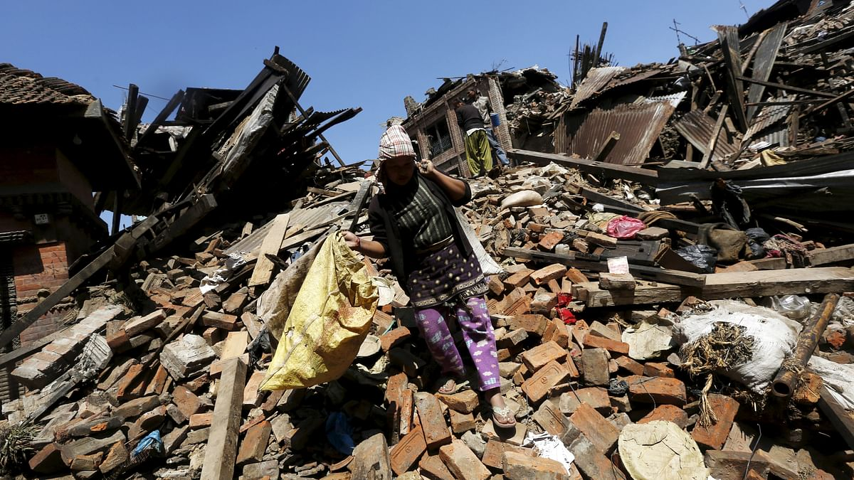 <!--StartFragment-->A woman carries her belongings as she walks over collapsed house after earthquake in Bhaktapur, Nepal. (Photo: Reuters)<!--EndFragment-->