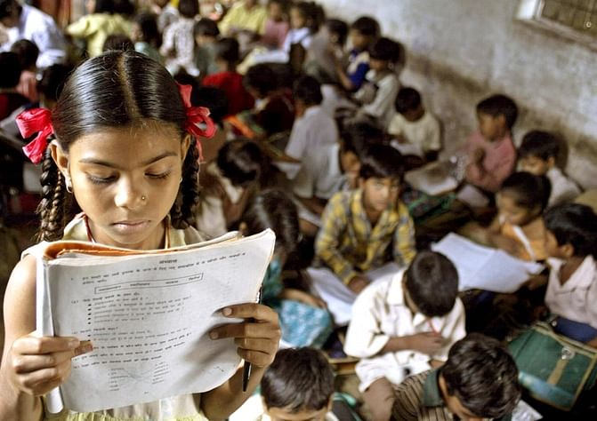 An Indian school girl reads her book inside her class at a government-run school. (Photo: Reuters)