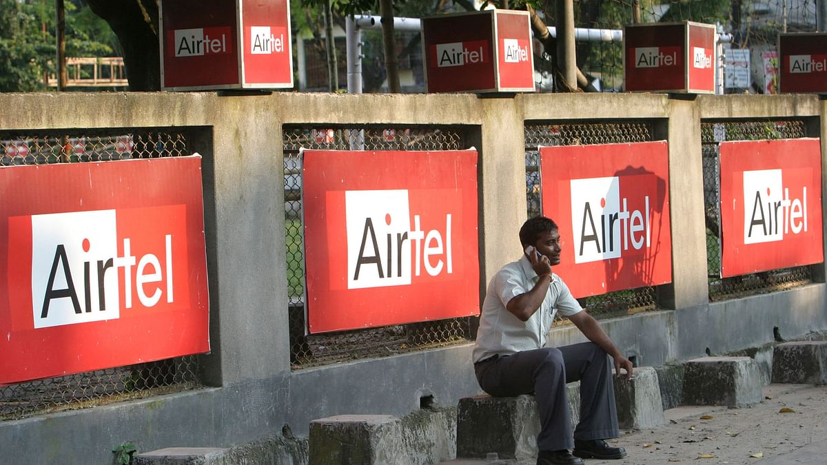A man talks on a mobile phone in front of Bharti Airtel hoardings in the eastern Indian city of Siliguri.