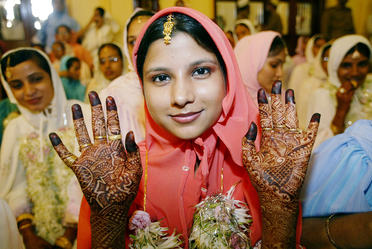 A young Muslim bride belonging to the Dawoodi Bohra community displays her henna-painted palms while waiting for proceedings during a mass wedding in Mumbai.