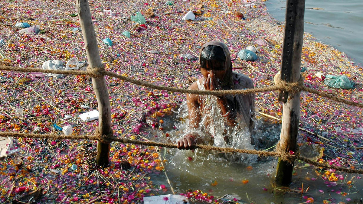 A devotee takes a dip in the much polluted river Ganga which is believed to wash away all sins. (Photo: Reuters)
