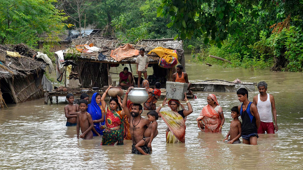 Flood-affected villagers carry their belongings  after heavy rains at Patna district in Bihar onAugust 29, 2013. (Photo: Reuters)