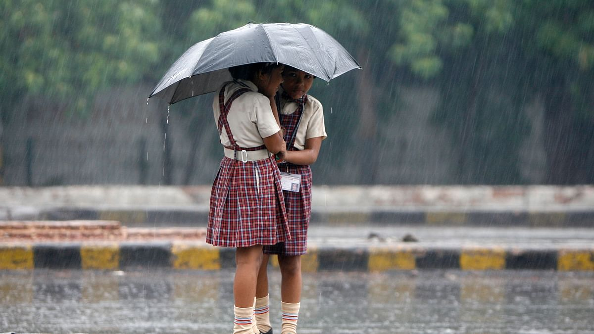 Schoolgirls stand on a road divider as they huddle under an umbrella during monsoon rain.