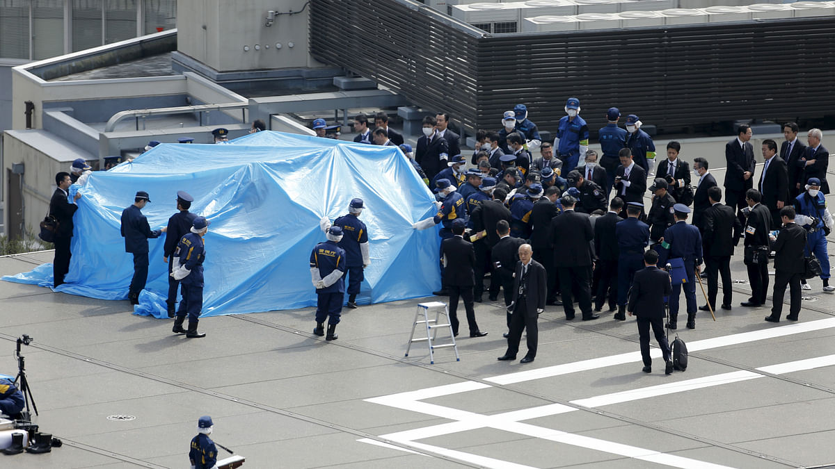Police and security officials stand around a tarpaulin covering a drone on the roof of JapanesePrime Minister Shinzo Abe's official residence in Tokyo. (Photo: Reuters)