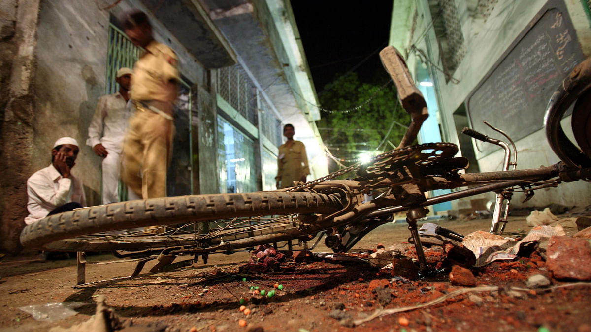 People walk past a damaged bicycle lying at a blast site inside a mosque in Malegaon, 260 km northeast of Mumbai 9 September.(Photo: Reuters)