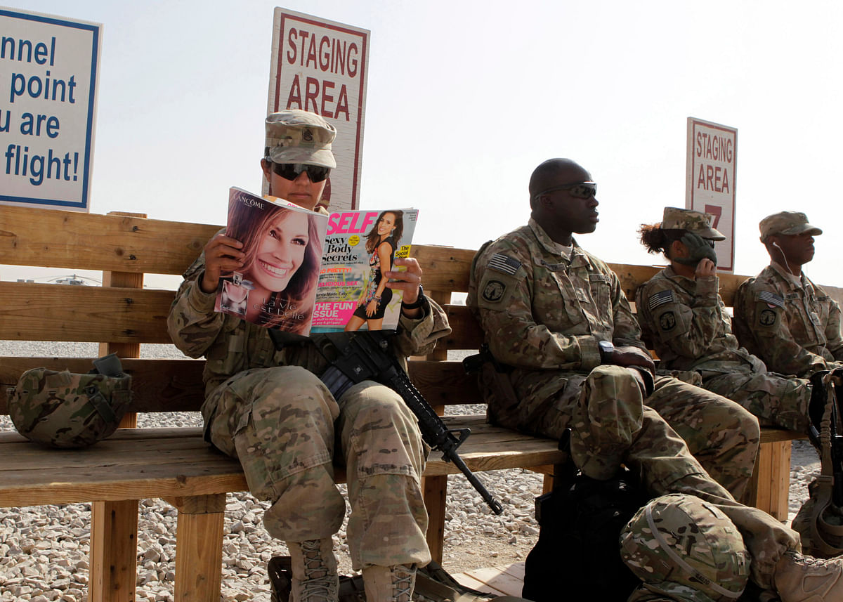 <!--StartFragment-->US Army soldier SSG Norma Gonzales of 426 Civil Affairs Battalion reads a magazine next to fellow soldiers while waiting to be ferried by a helicopter to different US military bases in Kandahar, southern Afghanistan. (Photo: Reuters)<!--EndFragment-->