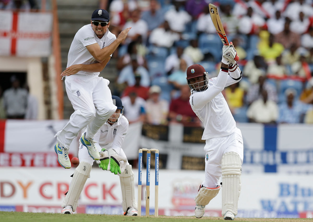 England captain Alistair Cook jumps to avoid being hit by a shot played by West Indies' Marlon Samuels, right, from a delivery of Moeen Ali during day one of their second Test match in Grenada, (Photo: AP)