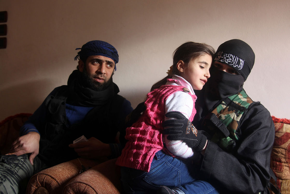 <!--StartFragment-->Um Jaafar, a woman fighter in the Free Syrian Army, sits with her husband Abu Jaafar, a Sawt al-Haq (Voice of Rights) battalion commander, and her daughter Faten at their home in Aleppo, February 12, 2013. (Photo: Reuters)<!--EndFragment-->