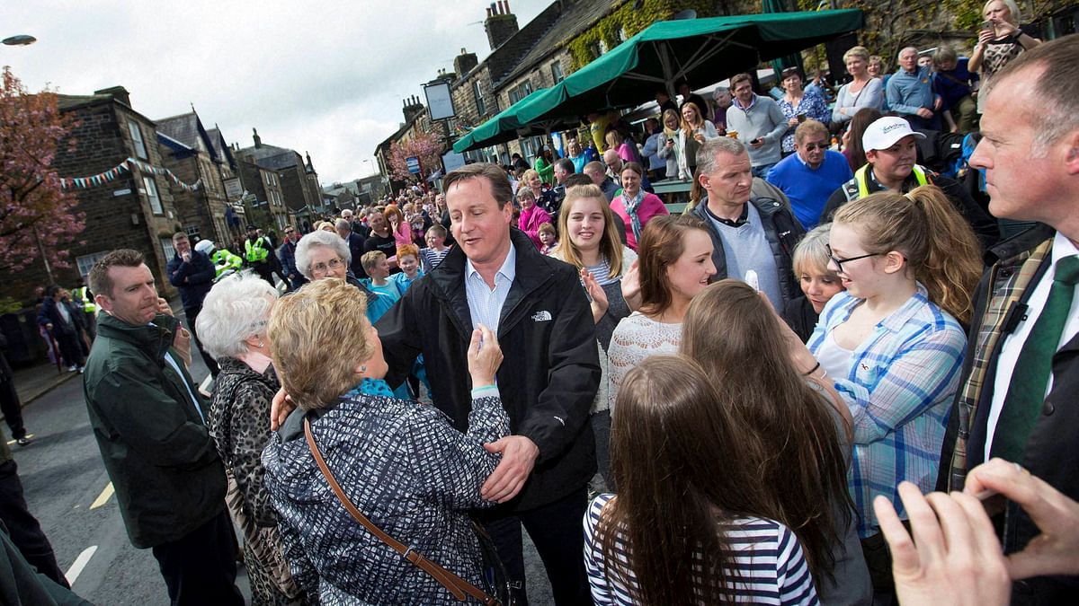British Prime Minister David Cameron goes to hug a member of the public during General Election campaigning in the lead up to the parliamentary elections on May 7. (Photo: PTI)