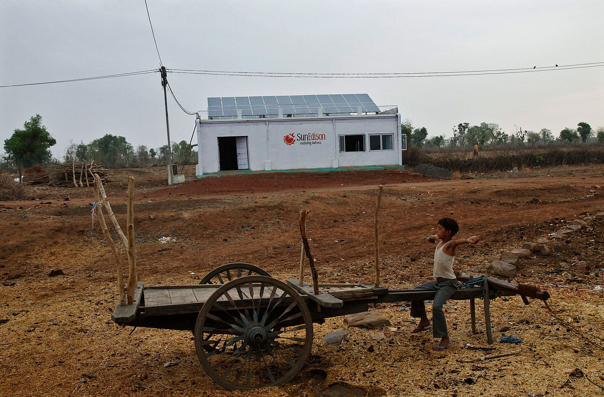 A boy sits on a cart in front of a solar power plant at Meerwada village of Guna district in the central Indian state of Madhya Pradesh. (Photo: Reuters)