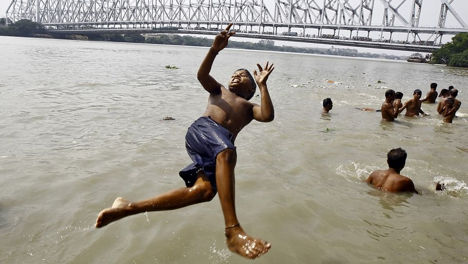 A boy jumps into River Ganga river to cool himself off on a hot summer day in Kolkata. Temperature in Kolkata on Wednesday is expected to reach 37 degree Celsius, according to India's met department.  REUTERS/Rupak De Chowdhuri - RTX1BS0B
