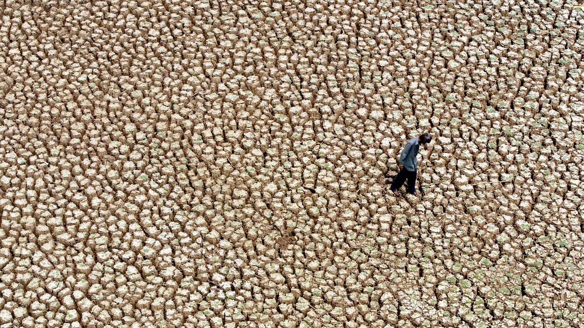Fisherman walks on a dry lake bed near Hyderabad. (Photo: Reuters)