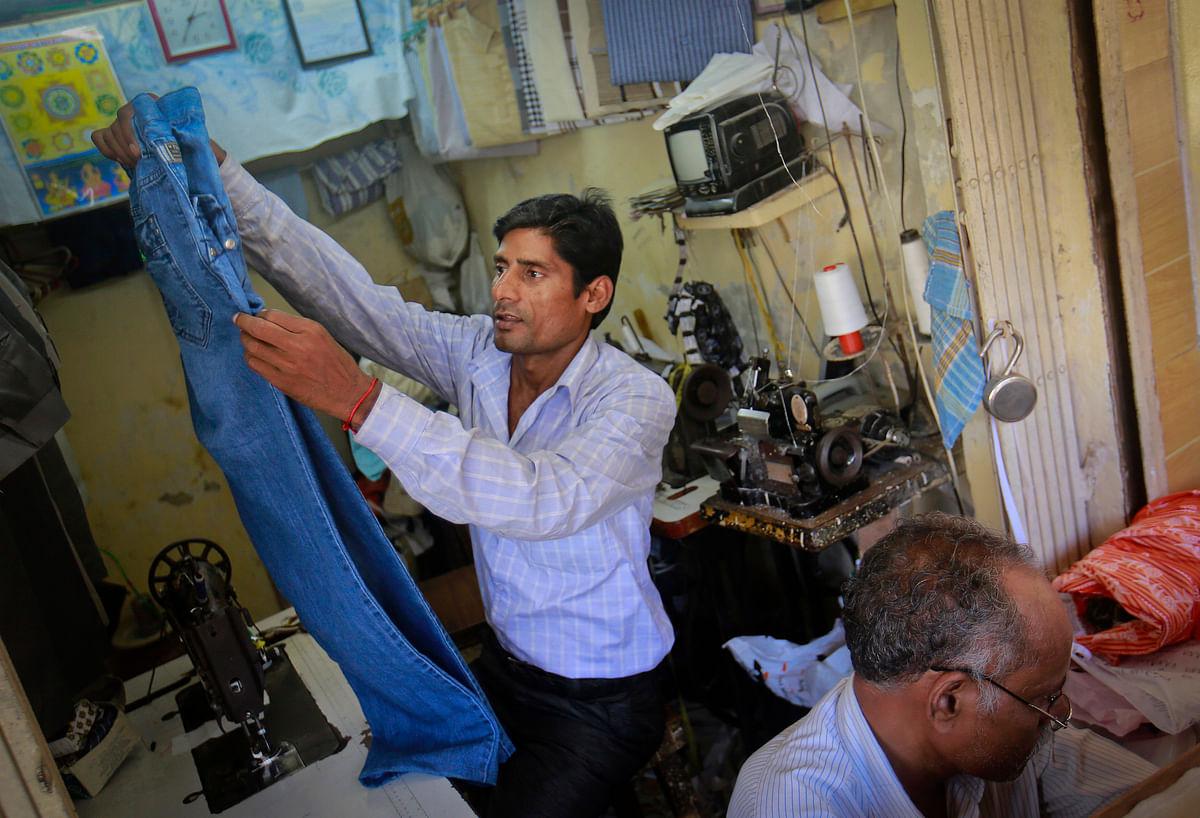 Ram Pratap Verma, a 32-year-old aspiring Bollywood film actor, alters a pair of trousers in a tailor shop in Mumbai. (Photo: Reuters)<!--EndFragment-->