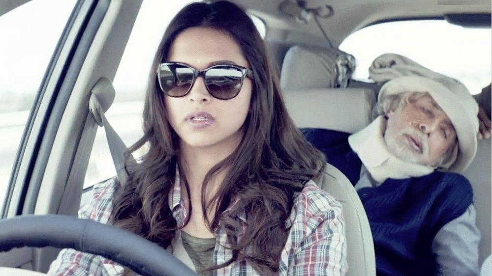 Deepika Padukone drives while Amitabh Bachchan naps in a scene from Shoojit Sarkar's <i>Piku</i>