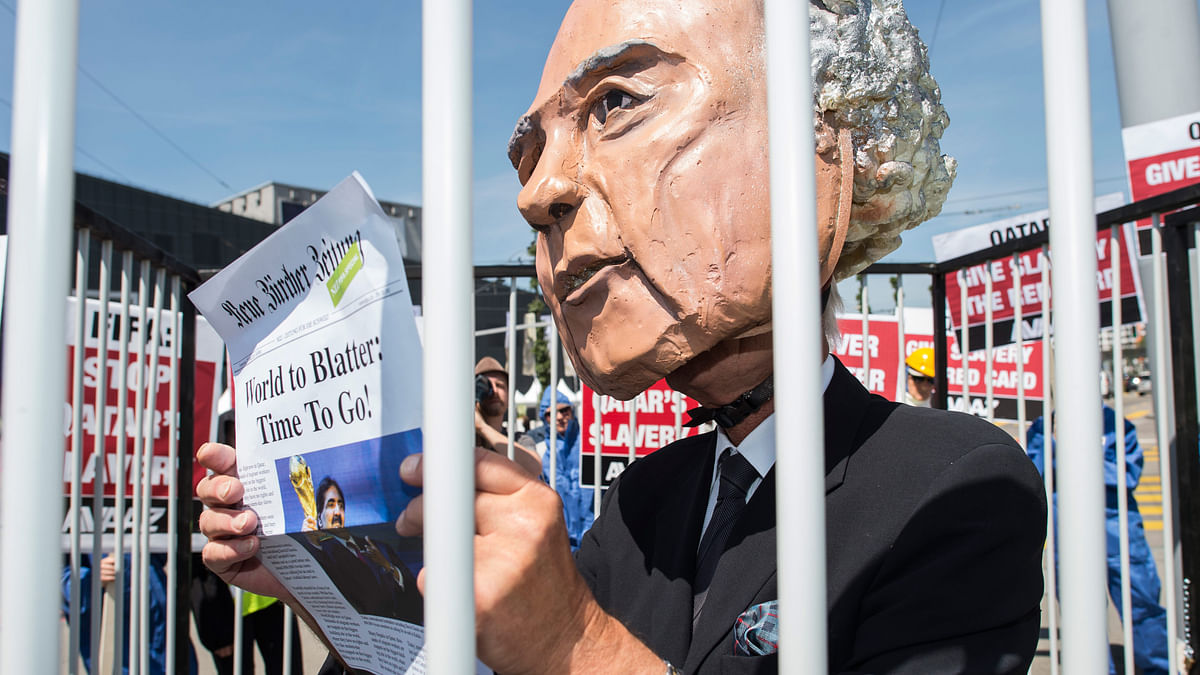 An activist with a giant mask of of FIFA President Sepp Blatter holds a front page as he stands in a cage during a protest. (Photo: AP)
