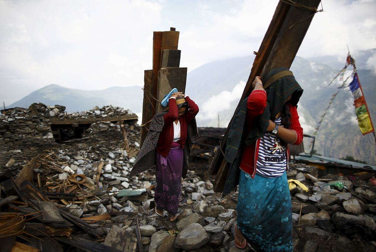 An earthquake victim, carrying a tin roof to rebuild a house, walks along the entrance gate of Barpak village at the epicenter of the April 25 earthquake in Gorkha district, Nepal. (Photo: Reuters)