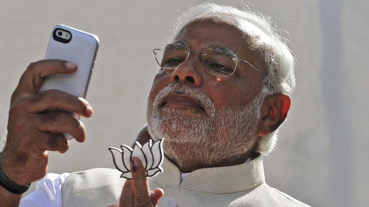 Prime Minister Narendra Modi clicks his famous selfie with the BJP party symbol, after casting his vote in Ahmadabad. last year (Photo AP).