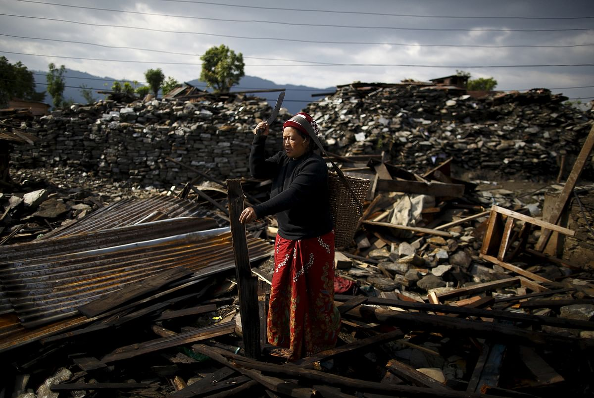 An earthquake victim cuts wood from the debris of her house in Barpak village at the epicenter of the April 25 earthquake in Gorkha district, Nepal. (Photo: Reuters)