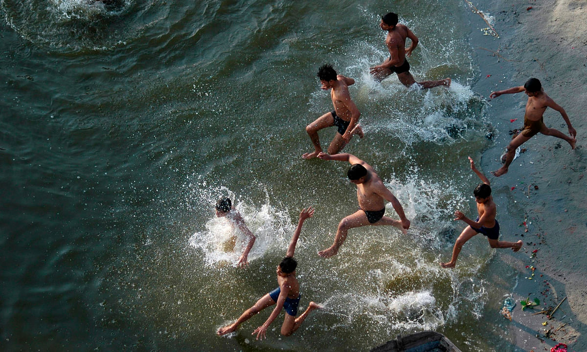 Boys play in the waters of the River Ganges in Allahabad to get respite from the heat. (Photo: Reuters)