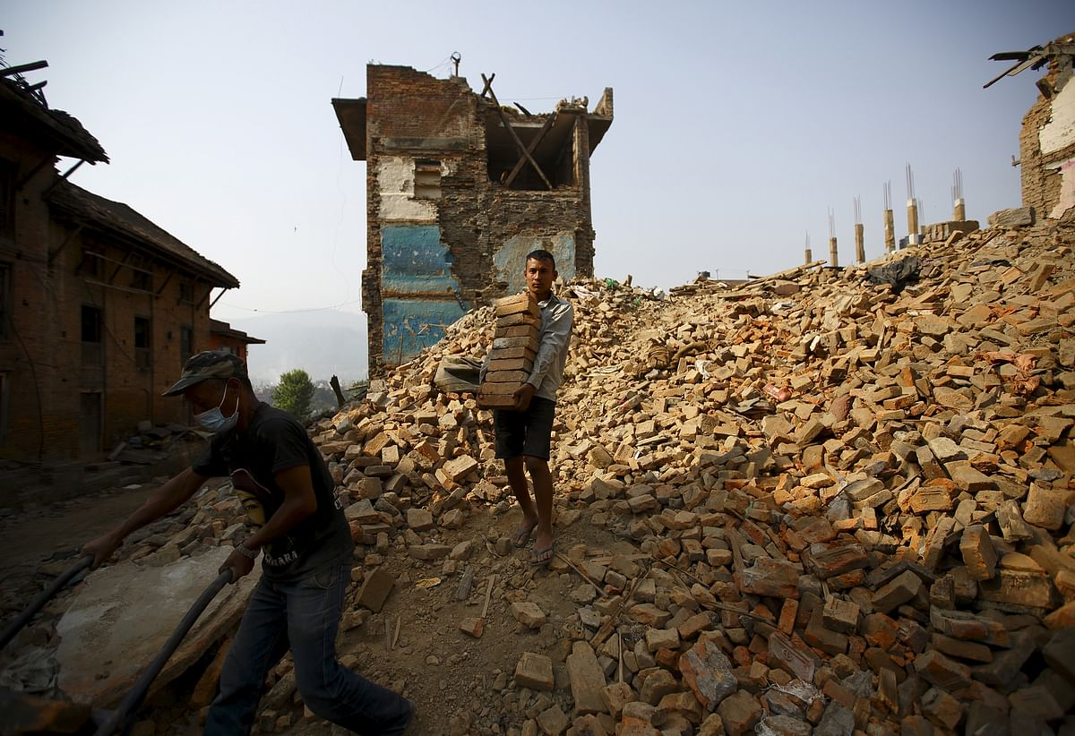 A man carries bricks from collapsed houses, a month after the April 25 earthquake in Bhaktapur, Nepal. (Photo: Reuters)
