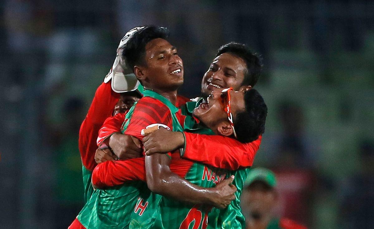 Bangladesh's Mustafizur Rahman, left,  celebrates with teammates Nasir Hossain, right, and Shakib Al Hasan, center, the dismissal of Ravichandran Ashwin. (Photo: AP)