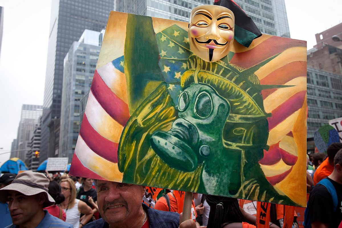 "A protester carries a sign with an image of the Statue of Liberty wearing a gas mask as he takes part in the ""People's Climate March"" down 6th Ave. in the Manhattan borough of New York, September, 2014. (Photo: Reuters)"