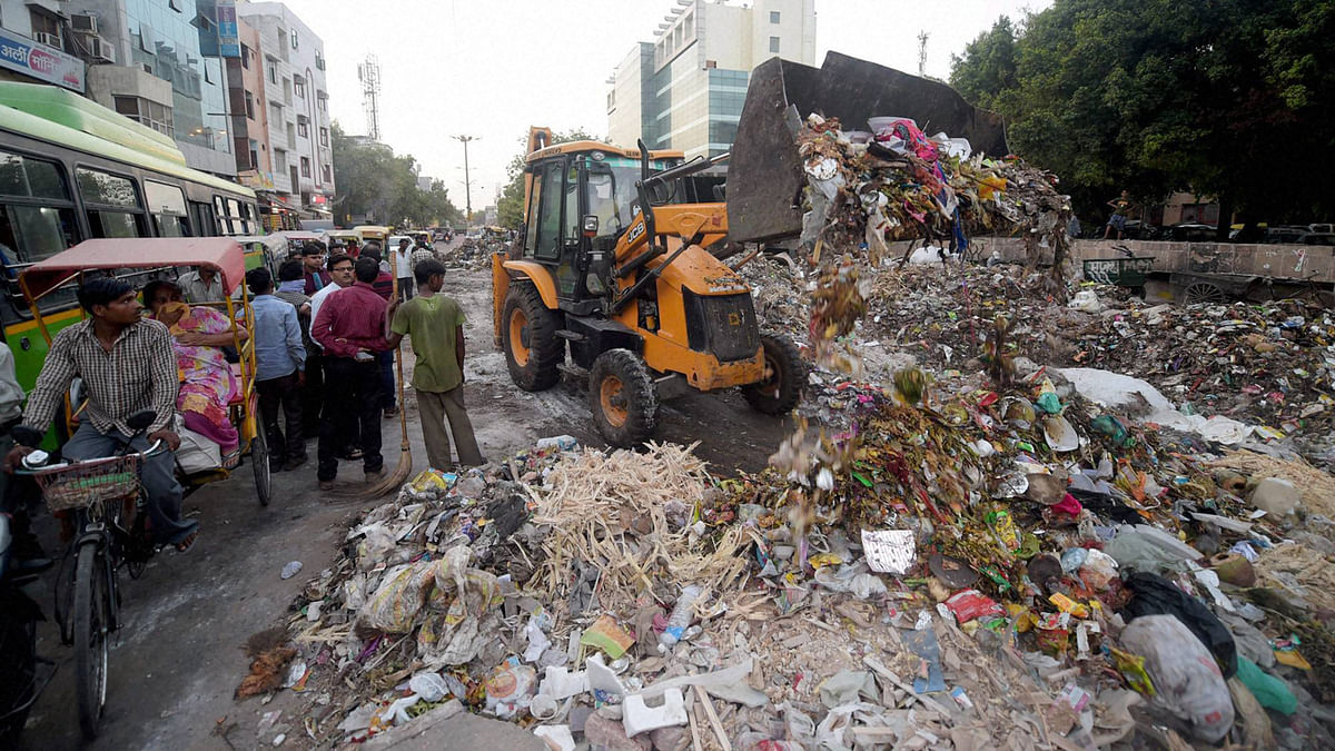 MCD workers cleaning up the garbage. (Photo: PTI)
