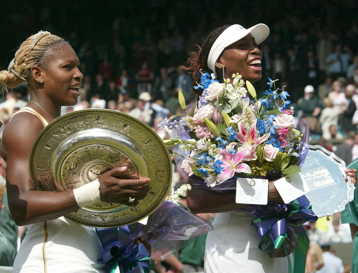 In this July 6, 2002 photo, Serena Williams, left, holds her trophy after defeating her sister Venu to win the Final. Following wins at the Australian and French Opens, Serena can become the fourth woman to win the calendar Grand Slam this year. Serena has to date won a totel of 20&nbsp;&nbsp;Grand Slam singles titles. (Photo: AP)<a></a>