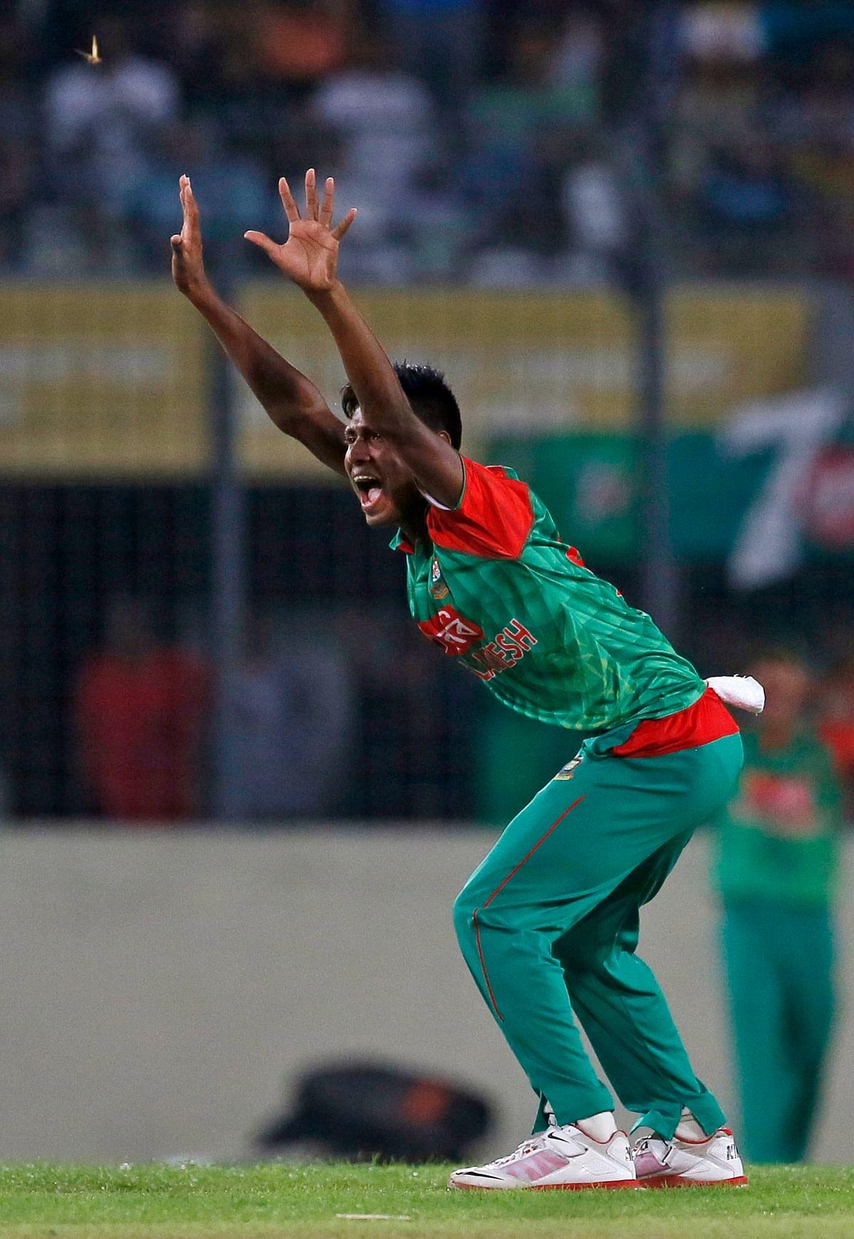 Bangladesh's Mustafizur Rahmancelebrates the dismissal of India's Rohit Sharma.