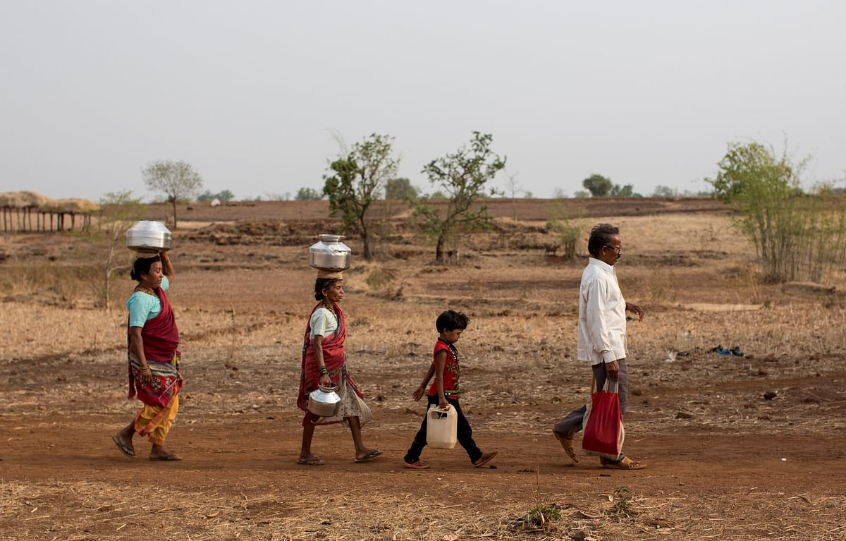 Bhaagi (L) and Sakhri (2nd from L), wives of Sakharam Bhagat (R) walk to fetch water from a well outside Denganmal village, Maharashtra, India, April 20, 2015. (Photo: Reuters)