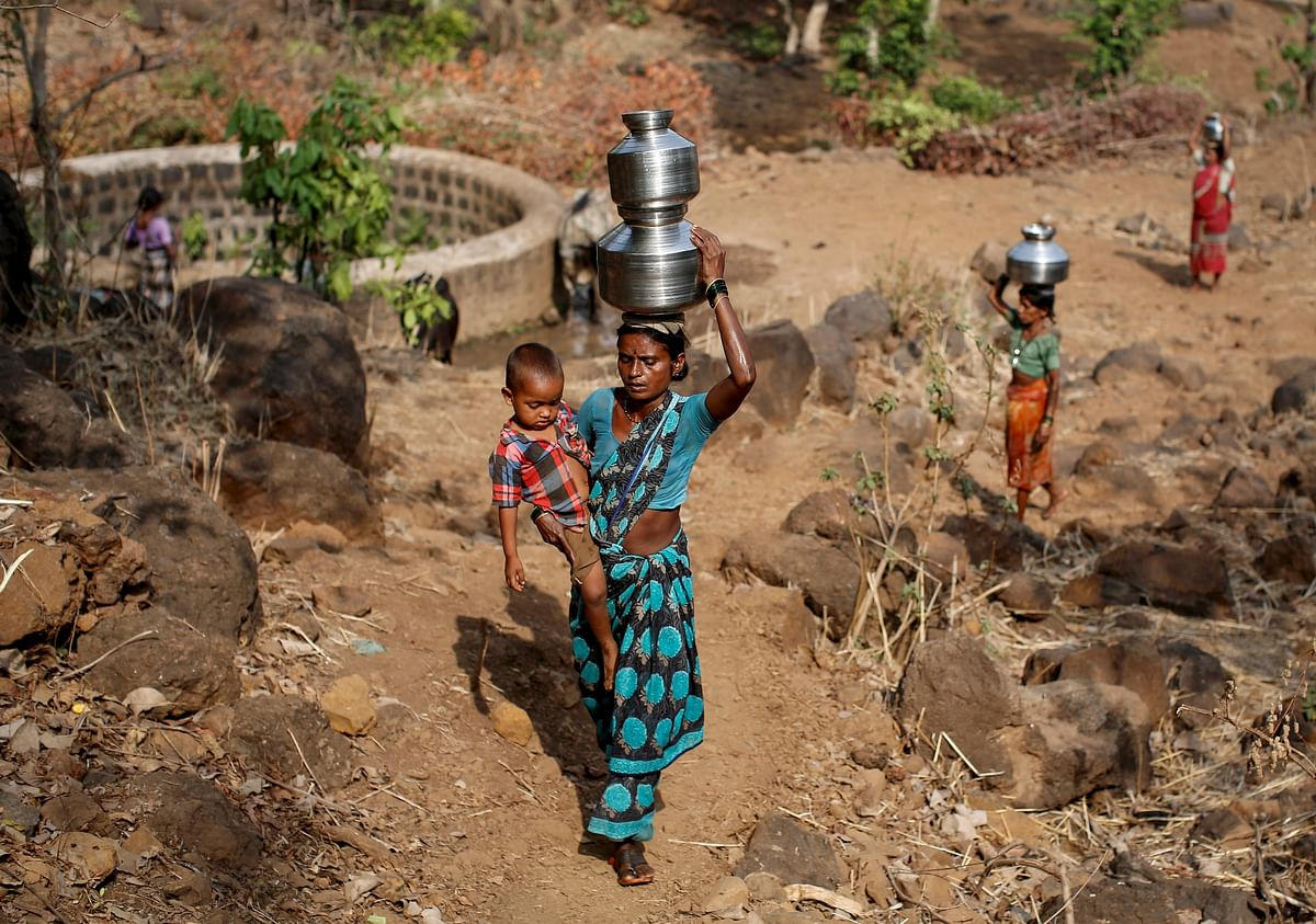 Shivarti, the second wife of Namdeo, holds her grandson while carrying metal pitchers filled with water from a well outside Denganmal village, Maharashtra, India, April 21, 2015. (Photo: Reuters)