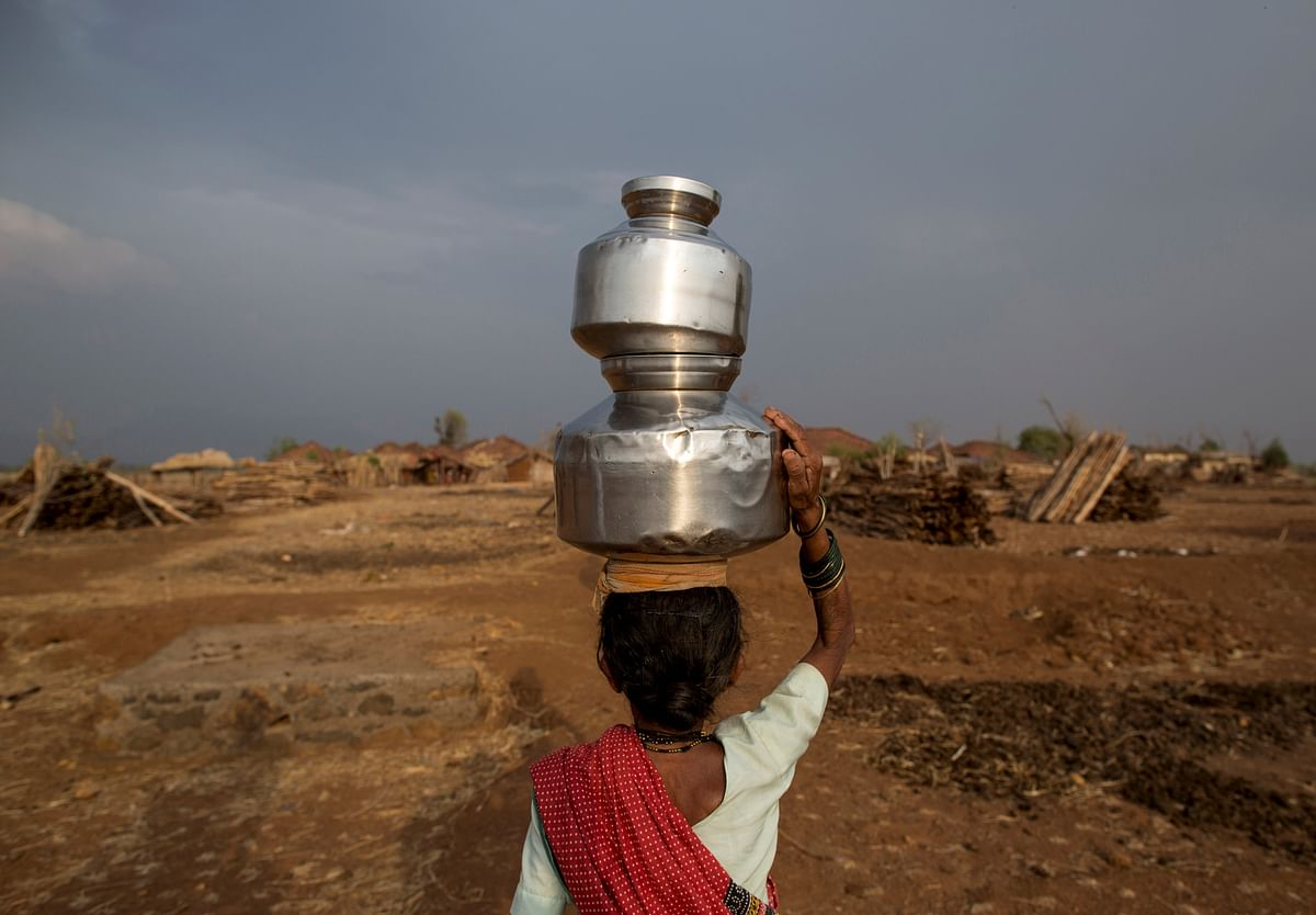 Sakhri, the second wife of Sakharam Bhagat carries a metal pitcher filled with water from a well outside her village in Denganmal, Maharashtra, India, April 20, 2015. (Photo: Reuters)
