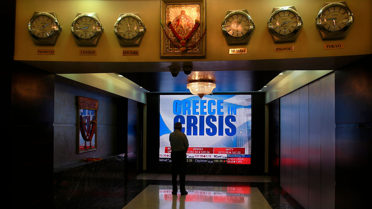 A man watches a television screen showing news of the Greece crisis at the Bombay Stock Exchange (BSE) office in Mumbai, India, Monday, June 29, 2015.  (Photo: AP)